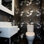 This powder room has a botanical theme, with architecture, bathroom, ceiling, floor, interior design, plumbing fixture, public toilet, room, toilet, wall, black