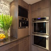 Mid-toned  quartered maple cabinetry provides a calming cabinetry, countertop, home appliance, interior design, kitchen, room, brown, black
