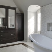 Armoire-style cabinetry in dark hickory wood provides storage bathroom, bathroom accessory, bathroom cabinet, floor, flooring, home, interior design, room, gray, black