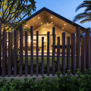 A palisade fences with irregular pickets separates the architecture, estate, facade, fence, grass, home, home fencing, house, landscape lighting, lighting, outdoor structure, property, real estate, residential area, black