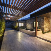 An hotel-style porte-cochere, paved in travertine, features natural architecture, backyard, courtyard, estate, facade, home, house, interior design, landscape lighting, lighting, outdoor structure, patio, property, real estate, residential area, roof, black