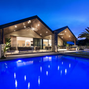 The reinvented home shows no trace of its architecture, estate, family car, home, house, leisure, lighting, property, real estate, reflection, residential area, resort, resort town, sky, swimming pool, villa, blue