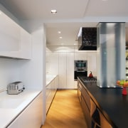 Most of the serious work in the kitchen architecture, cabinetry, ceiling, countertop, daylighting, floor, flooring, hardwood, house, interior design, kitchen, real estate, room, wood flooring, gray