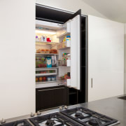 Appliances are fully concealed behind co-planar doors in interior design, white