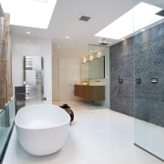 The wet-area shower has a floor-to-ceiling pebble wall. architecture, bathroom, estate, floor, flooring, interior design, product design, property, real estate, tile, gray