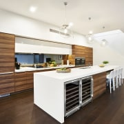 White benchtops and woodgrain laminate feature in this cabinetry, ceiling, countertop, cuisine classique, floor, flooring, hardwood, interior design, kitchen, laminate flooring, real estate, wood, wood flooring, white, brown
