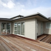 The large wood deck of this show home elevation, estate, facade, home, house, property, real estate, residential area, roof, siding, window, white