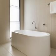 A curvaceous bathtub takes pride of place in bathroom, bathroom sink, bathtub, bidet, ceramic, floor, flooring, interior design, plumbing fixture, product design, room, sink, tap, tile, toilet seat, wall, gray, brown