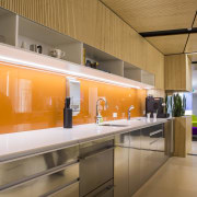 Orange colourbacked glass features behind the kitchen cabinetry countertop, interior design, kitchen, orange, brown