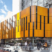 This timber facade curves around the plaza at architecture, building, city, commercial building, facade, metropolis, metropolitan area, mixed use