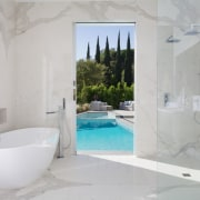 In this new bathroom, a pocket door slides bathroom, bathtub, estate, floor, home, interior design, plumbing fixture, property, room, tile, wall, gray