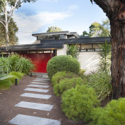 Mid-century Modern home renovation in Melbourne retains original arecales, backyard, estate, garden, grass, home, house, landscape, landscaping, outdoor structure, plant, property, real estate, tree, walkway, yard, brown