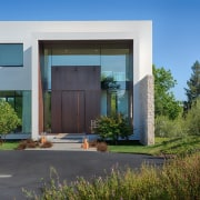 The bronze front door has a matching surround, architecture, estate, facade, grass, home, house, property, real estate, residential area, sky, window, teal