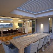 Beautiful alfresco covered by operable louvre to maintain ceiling, daylighting, dining room, estate, floor, flooring, house, interior design, property, real estate, table, window, wood, gray, brown