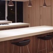 Kitchen island in Navurban Hazlewood and Corian - cabinetry, countertop, floor, flooring, furniture, interior design, kitchen, light fixture, lighting, product design, table, wood, red
