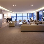 The formal living area includes a bar clad ceiling, floor, flooring, interior design, living room, penthouse apartment, real estate, window, brown