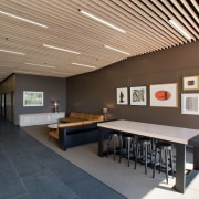 A timber batten ceiling conceals services in the architecture, ceiling, daylighting, furniture, interior design, table, gray, black