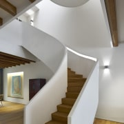 A dramatic sculptural staircase winds up all three architecture, ceiling, daylighting, floor, handrail, hardwood, home, house, interior design, product design, stairs, wood, gray