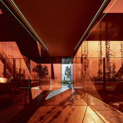 An orange-red glass box forms a transition zone architecture, evening, home, light, lighting, night, reflection, sky, tourist attraction, wood, red