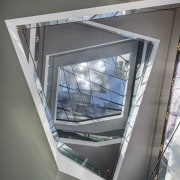 A huge cantilevered reflector frame on top of architecture, daylighting, glass, product design, structure, window, gray