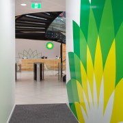 BP corporate signage is evident in the corridor architecture, ceiling, daylighting, floor, flooring, green, interior design, product design, wall, gray