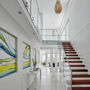 A cantilevered staircase appears to float in the architecture, ceiling, daylighting, floor, interior design, lobby, gray