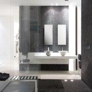 Simple geometric Gessi Segni showerheads, available in round, bathroom, bathroom accessory, floor, flooring, interior design, product design, room, sink, tile, wall, gray