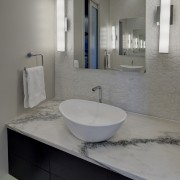 Textural white rock features on the floor of architecture, bathroom, bathroom accessory, bathroom cabinet, floor, interior design, plumbing fixture, product design, room, sink, tap, gray