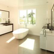 A freestanding soaking tub divides this master bathroom bathroom, estate, floor, flooring, home, interior design, property, real estate, room, tile, yellow, brown