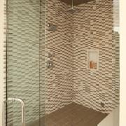 This double shower features multiple showerheads. Floor and bathroom, floor, flooring, glass, plumbing fixture, room, shower, tile, brown, orange