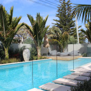Glass safety fences and stone stepping stones from arecales, backyard, estate, landscaping, leisure, palm tree, plant, property, real estate, resort, swimming pool, tree, villa, water, water feature, teal