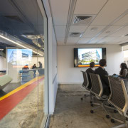 Glass walls separate the meeting rooms from the office, passenger, gray