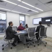 A trapezoidal table in the video-conferencing room of electronic device, institution, office, technology, gray