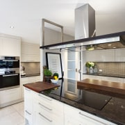 A removable wood prep board is integrated into countertop, cuisine classique, interior design, kitchen, real estate, white