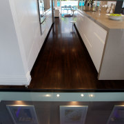 This glass floorplate lets guests admire the well-stocked countertop, daylighting, floor, flooring, glass, hardwood, interior design, property, gray, black