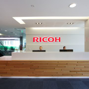 Timber reception desk in the new Ricoh office interior design, lobby, gray