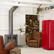 A bright red Smeg FAB28 refrigerator is the chair, floor, flooring, furniture, home, interior design, living room, loft, white
