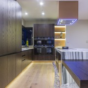 A bank of four black Smeg ovens is apartment, architecture, ceiling, countertop, floor, flooring, hardwood, house, interior design, kitchen, real estate, room, wood, wood flooring, gray