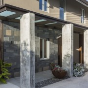 The main entrance to this renovated house is door, facade, home, house, porch, real estate, residential area, siding, window, black, gray