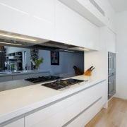 A mirrored splashback adds visual depth to this architecture, countertop, house, interior design, kitchen, real estate, white, gray