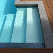 This new pool by Mayfair Pools features blue-toned azure, daylighting, floor, roof, swimming pool, wall, water, wood, wood stain, teal, brown