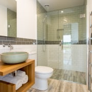 This bathroom teams a glass shower stall with architecture, bathroom, floor, flooring, home, interior design, real estate, room, tile, wall, wood flooring, white