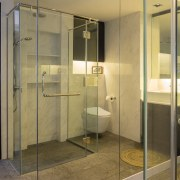 Glass walls screen the bathroom in the master bathroom, interior design, room, brown