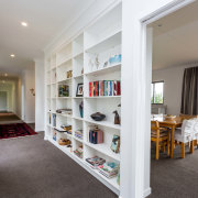 When is a hallway not a hallway? This bookcase, flooring, interior design, property, real estate, shelf, shelving, gray, white