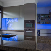 This kitchen has blue back-lit colour panels from display device, interior design, black, gray, blue