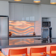 This kitchen has blue back-lit colour panels from interior design, orange, gray