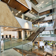 A grand atrium forms a vertical spine on architecture, daylighting, interior design, lobby, stairs, gray, brown