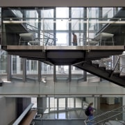 :The main circulation stair in this educational facility architecture, building, condominium, daylighting, glass, handrail, mixed use, stairs, structure, gray, black