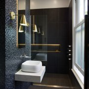 LED lights tucked behind the vanity mirror and architecture, bathroom, floor, flooring, home, interior design, plumbing fixture, room, tile, toilet, wall, black, gray