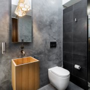 This discreet bathroom by designer Joe Chindarsi is bathroom, bathroom accessory, bathroom cabinet, ceramic, floor, interior design, plumbing fixture, product design, room, sink, tap, tile, wall, gray, black, white